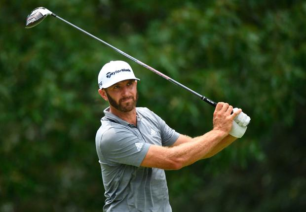 Dustin Johnson watches his tee shot on the 7th hole
