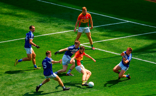 Diarmuid Walshe of Carlow shoots for goal before being blocked down by Damien O'Connor of Laois, right
