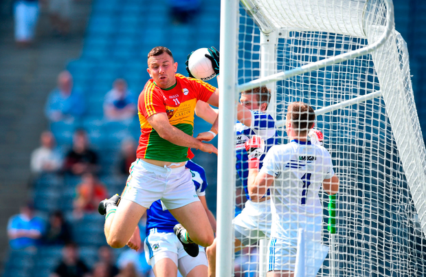 Mark Timmons of Laois comes to the rescue of goalkeeper Graham Brody by making a great catch under pressure from Carlow's Darragh Foley. Photo by Stephen McCarthy/Sportsfile