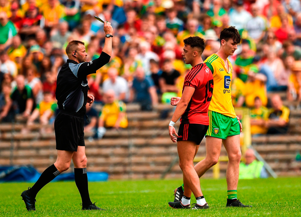 Referee Anthony Nolan issues yellow cards to Ryan Johnston of Down and Michael Langan of Donegal. Photo by Oliver McVeigh/Sportsfile