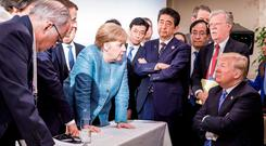The German government released this picture of Chancellor Angela Merkel, with France's President Macron to her right, speaking to a seated US President Donald Trump at the G7 Summit in La Malbaie, Quebec, Canada, on Saturday. Photo: Jesco Denzel/German Federal Government via AP