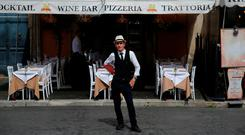 A waiter stands in front of a restaurant in Piazza Navona in Rome, Italy. Photo: Tony Gentile/Reuters