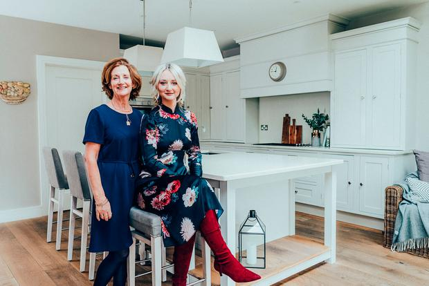 Interior designer Lauren Martin with her mother, Christine, in the kitchen of the Martins' new home in south Co Dublin. The units are from the Panelling Centre, but Lauren customised them with beading. The marble island top is extra large as they felt the island in their last house was too small. The new size is a success.
