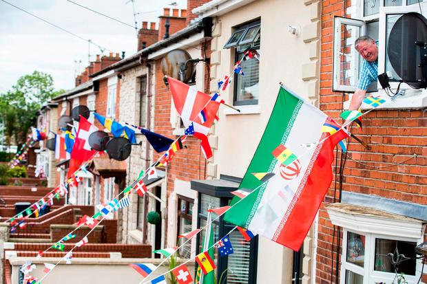 Gerry Sloan hangs out his bedroom window to unravel the Iranian flag outside his home at Whiterock Gardens in West Belfast as he and others residents have gotten into the World Cup fever to create a sweepstakes and raise funds for a street party on the day of the World Cup Final. Liam McBurney/PA Wire