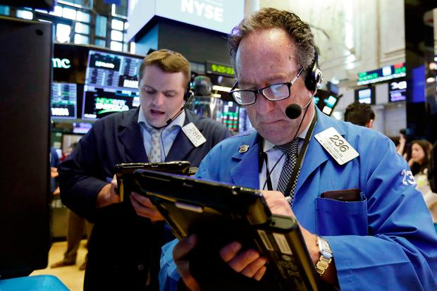 Traders Steven Kaplan, right, and Michael Milano works on the floor of the New York Stock Exchange. Photo: AP