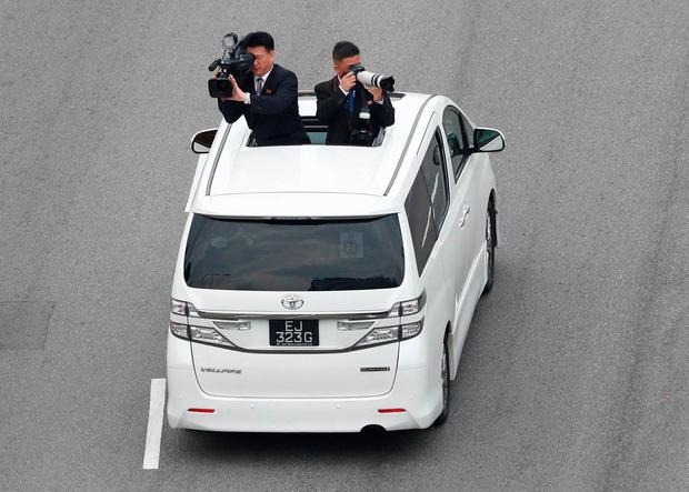 Official cameramen follow the motorcade of North Korean leader Kim Jong Un travels towards Sentosa for his meeting with US President Donald Trump, in Singapore