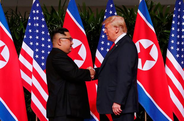 US President Donald Trump shakes hands with North Korean leader Kim Jong Un at the Capella Hotel on Sentosa island in Singapore