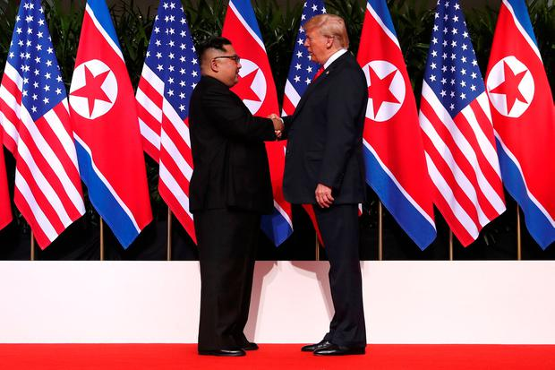 U.S. President Donald Trump and North Korea's leader Kim Jong Un shake hands during a summit at the Capella Hotel on the resort island of Sentosa, Singapore June 12, 2018. REUTERS/Jonathan Ernst