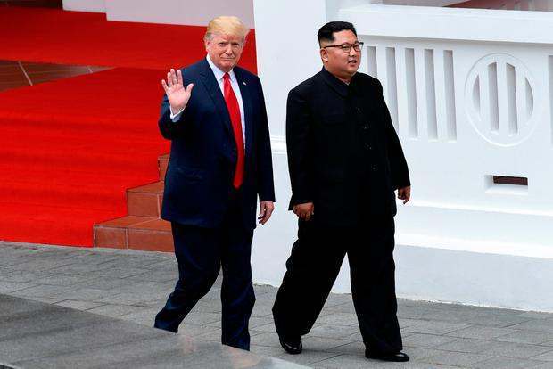U.S. President Donald Trump waves as he walks with North Korean leader Kim Jong Un in the Capella Hotel after their working lunch, on Sentosa island in Singapore June 12, 2018. Susan Walsh/Pool via Reuters