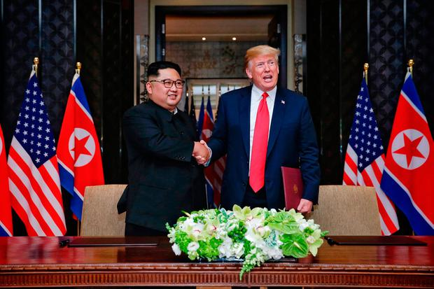 Singapore Government pool photo from the US - North Korea summit of a signing ceremony between US president Donald Trump and leader of North Korea, Kim Jong-un, at Capella, Singapore. Kevin Lim/The Straits Times/PA Wire