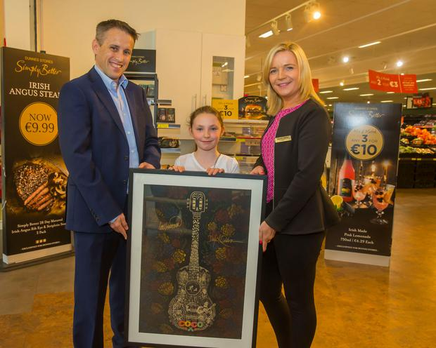 11/06/2018. Pictured at Dunnes Stores in Dungarvan, Co Waterford is Mary-Kate Owens Bourke from Youghal who was the winner of the Disney Coco poster, also pictured are David Hartnett, Independent Retail Sales Manager and Angie Cashin Dunne Stores Store manager. Picture: Patrick Browne