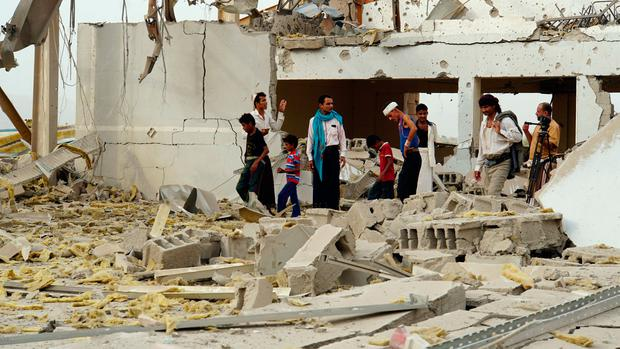 People inspect damage at a Doctors Without Borders medical facility after it was hit by an air strike in Abss, Yemen.