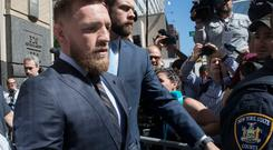 Conor McGregor is escorted by court officers as he leaves a Brooklyn Supreme court, Thursday, June 14, 2018, in New York. McGregor is in plea negotiations to resolve charges stemming from a backstage melee at a Brooklyn arena. The 29-year-old Irish fighter and co-defendant Cian Cowley remained free on bail after a brief court appearance on Thursday. They are due back in court July 26. (AP Photo/Mary Altaffer)