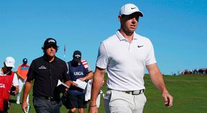 Rory McIlroy and Phil Mickelson walk to the 11th tee