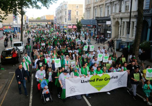 People take part in a silent walk by Grenfell Tower, to mark one year since the blaze which claimed 72 lives. Rick Findler/PA Wire