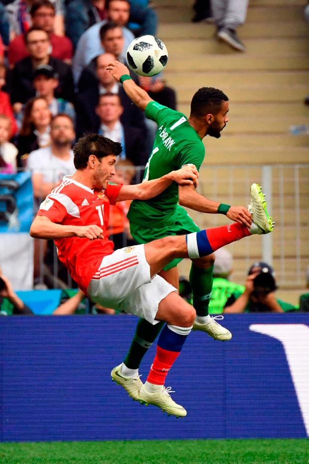 Russia's midfielder Yury Zhirkov (L) vies with Saudi Arabia's defender Mohammed Al-Breik. Photo: Getty Images