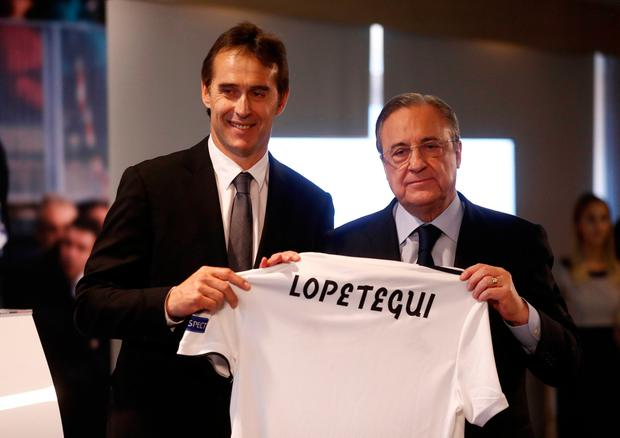 Julen Lopetegui poses with the jersey with Real Madrid president Florentino Perez after being unveiled as the club's new manager yesterday. Spain, who Lopetegui coached until Wednesday, begin their World Cup campaign against Portugal tonight. Photo: REUTERS/Juan Medina