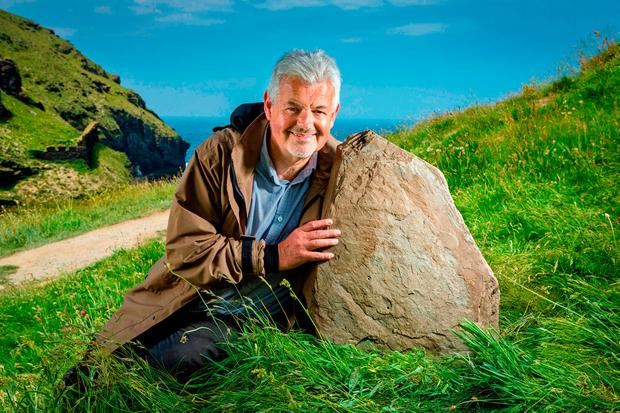Site curator Win Scutt with a stone inscribed with rare ancient writing. Photo: PA
