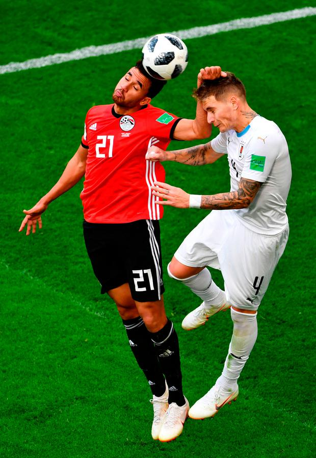 Trezeguet of Egypt challenge for the ball with Guillermo Varela of Uruguay Photo: Getty