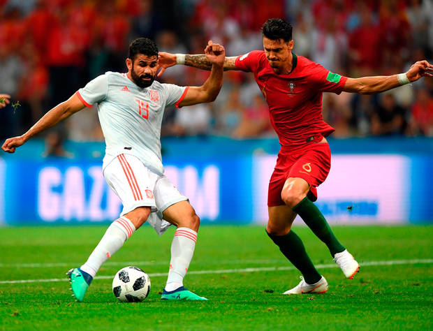 SOCHI, RUSSIA - JUNE 15: Spain striker Diego Costa shoots to score the first Spain goal despite the attentions of Jose Fonte during the 2018 FIFA World Cup Russia group B match between Portugal and Spain at Fisht Stadium on June 15, 2018 in Sochi, Russia. (Photo by Stu Forster/Getty Images)