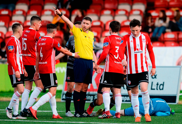 Referee Paul McLaughlin awards a free as Gerard Doherty of Derry City lies on the ground injured Photo: Oliver McVeigh/Sportsfile