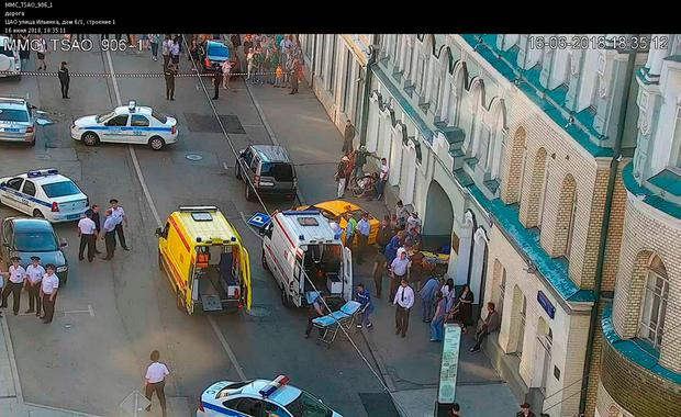 A handout CCTV picture released by the Moscow Municipal Traffic Regulation center CODD, shows Russian police officers and paramedics working at the scene, after a taxi drove into a crowd. Photo: AFP/Getty Images
