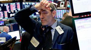 Trader Gregory Rowe feels the strain as he works on the floor of the New York Stock Exchange — US stocks fell with other markets around the world last Friday after the Trump administration stepped up the trade dispute with China. Photo: AP