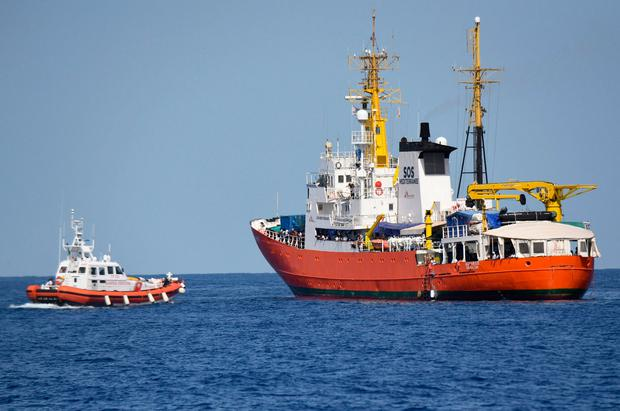 An Italian coastguard boat, left, approaches the refugee ship Aquarius in the Mediterranean last week. Photo: AP