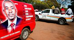 Vehicles display the logos for Zimbabwean opposition Movement For Democratic Change (MDC) party, and the ruling ZANU PF party outside an election nomination court in Harare, Zimbabwe last week. Photo: Reuters/Philimon Bulawayo