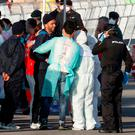 Migrants are met by emergency workers after descending the Italian coast guard vessel Dattilo upon arrival at the eastern port of Valencia, Spain (AP Photo/Alberto Saiz)