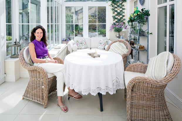 Jean in the romantically decorated sun room to the front of the house. Photo: Tony Gavin