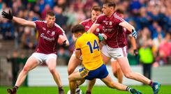 Diarmuid Murtagh of Roscommon is fouled by Galway's Thomas Flynn (No 9) and Eoghan Kerin, which resulted in a Roscommon penalty at Dr Hyde Park yesterday. Photo: Ramsey Cardy/Sportsfile