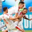 Serbia's Aleksandar Kolarov is swarmed by team mates after scoring their winning goal. (AP Photo/Mark Baker)
