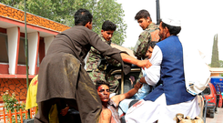Rescuers transport an injured man to a hospital after a car bomb in Jalalabad city, Afghanistan Photo: REUTERS/Parwiz