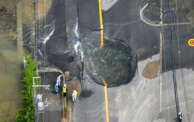 Water flows out from cracks in a road damaged by an earthquake in Takatsuki, Osaka prefecture, western Japan, in this photo taken by Kyodo June 18, 2018. kyodo/via REUTERS