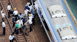 Passengers get off a train which operation was suspended after an earthquake in Takatsuki, Osaka prefecture, western Japan, in this photo taken by Kyodo June 18, 2018. Kyodo/via REUTERS