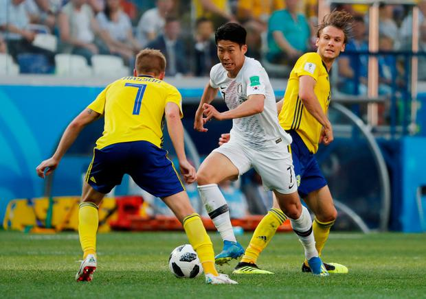 Son Heung-min looks for a way around Sweden's Sebastian Larsson. Photo: REUTERS/Carlos Barria
