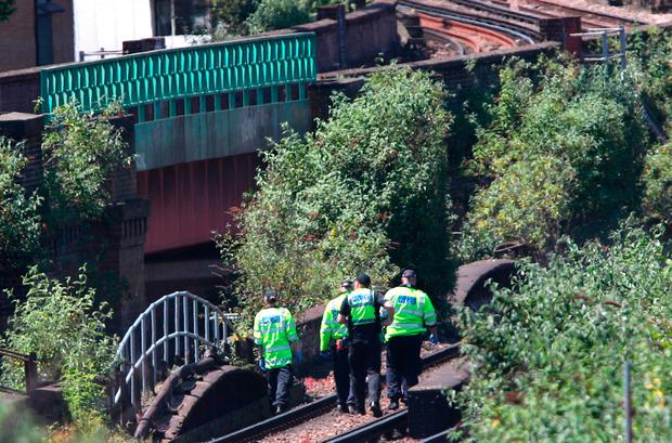 Police officers at the scene where three men died on a railway line in south London yesterday. Photo: PA