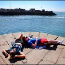 Soaking up the sun at Howth Pier during the sunny weather was Roisin Fleming from Donaghmeade and Dylan Cooling from Artane. Pic Steve Humphreys