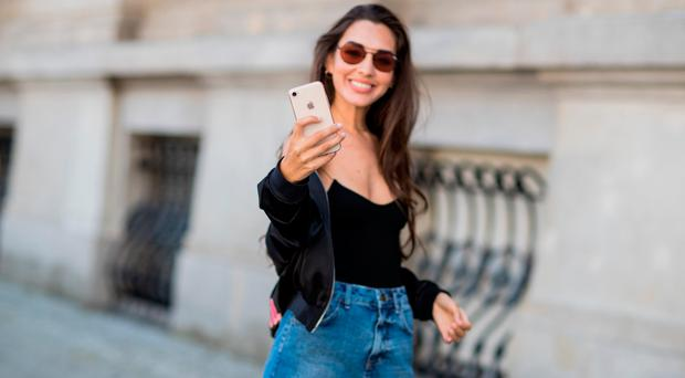 Model Dora Molina taking a photo with her iphone