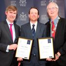 Shane Phelan, centre, receives his certificates from Law Society president Michael Quinlan and director general Ken Murphy. Photo: Lensmen