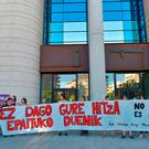 Demonstrators hold a banner in front of Pamplona's courthouse that reads