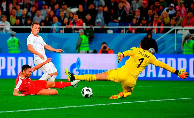 HERO: Switzerland's Xherdan Shaqiri slides the ball past Serbia's Vladimir Stojkovic for his late, late winner