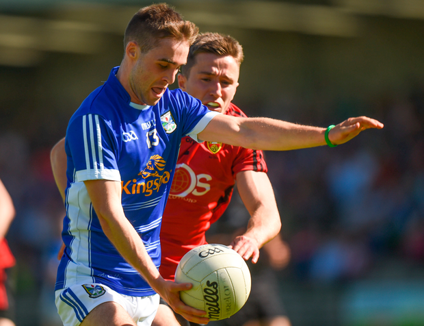 Cavan's Conor Bradley keeps the ball ahead of Down's Ryan McAleenan. Photo: Sportsfile