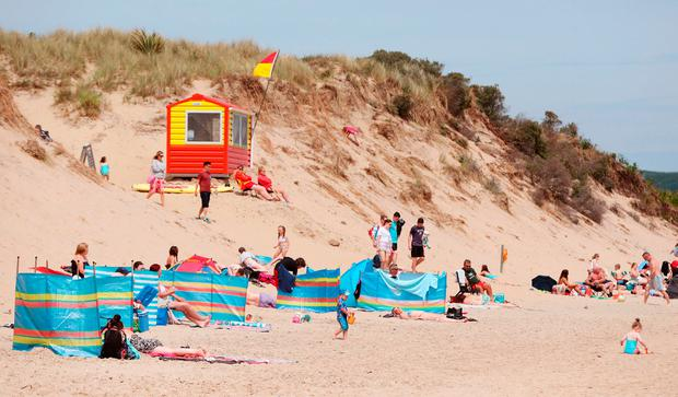 HOT: Sunbathers at Brittas Bay yesterday. Photo: Neil Carson