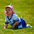 One-year-old Waterford supporter Fia White, from Dungarvan, enjoys the Fraher Field pitch after the game against Monaghan. Photo by Daire Brennan/Sportsfile