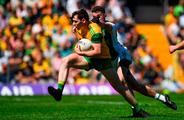 Jamie Brennan of Donegal is tackled by James McMahon of Fermanagh. Photo by Ramsey Cardy/Sportsfile