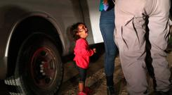 A mexican child cries after being detained by US border guards