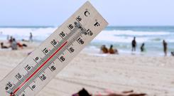 A temperature scale on a beach shows high temperatures during a heat wave.