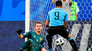 Russia's goalkeeper Igor Akinfeev (L) reacts as Luis Suarez celebrates Uruguay's second goal. Photo: AFP/Getty Images
